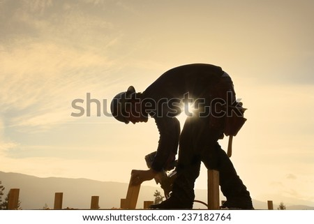 A carpenter working on a construction site - stock photo