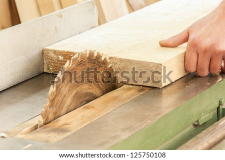 A carpenter  works on woodworking the machine tool. Carpenter working on woodworking machines in carpentry shop. - stock photo
