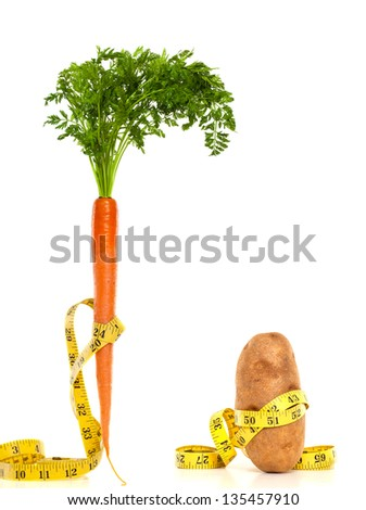 A carrot and potato with measuring tape around them. Diet concept - stock photo