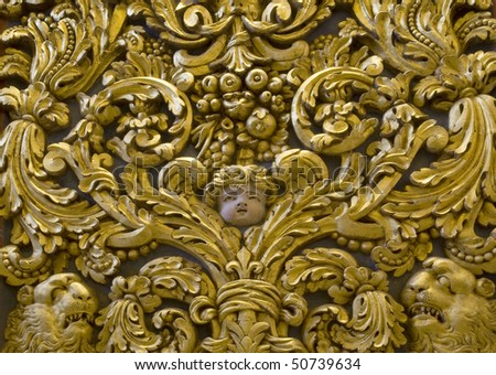 A carved relief with a face surrounded by lions and plants - stock photo