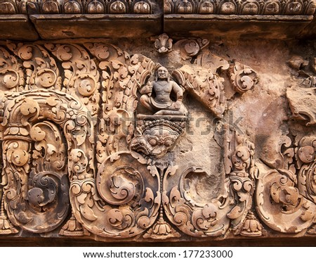 A carving of Buddha amidst other details above an entrance to one of the smaller buildings at the Banteay Srei temple near Angkor Wat.  - stock photo