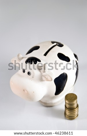 A cash cow/piggy bank, coins on the side, with copy-space