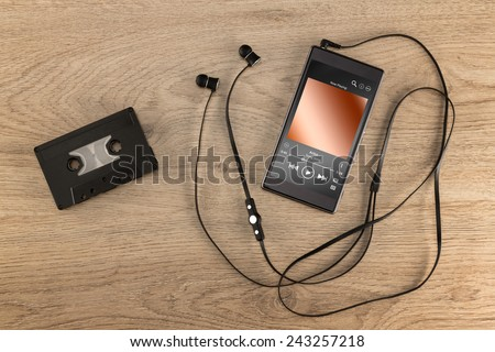 A cassette tape, the old way to listen to music compared to today's modern way to listen to music in a cell phone.   - stock photo