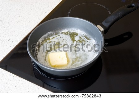 A cast iron pan with some butter - stock photo