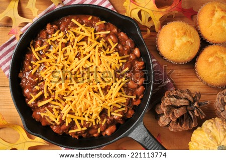 A cast iron skilled with chili con carne and cheddar cheese, from a high angle view - stock photo