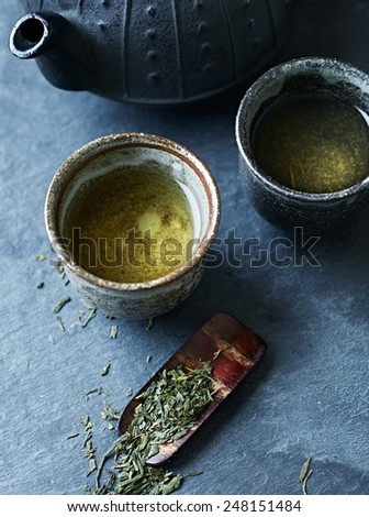 A cast iron tea pot and green tea in ceramic cups  - stock photo