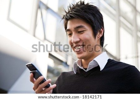 A casual asian businessman texting on his cell phone