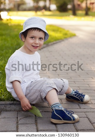 A casual outdoor portrait of a happy smiling child boy sitting on path in a park. - stock photo