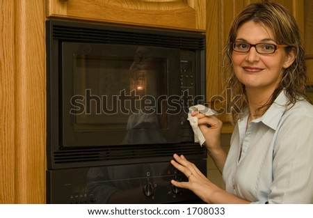 A casual women using a disinfectant wipe to clean the microwave oven.