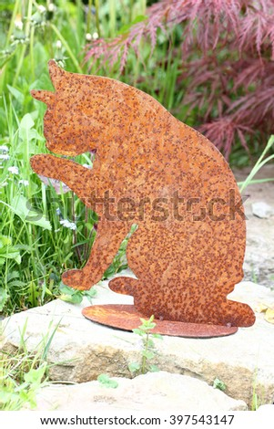 a cat made of rusted metal, placed as a decoration in the garden