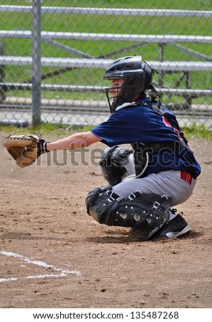 A catcher watches the pitch come in - stock photo