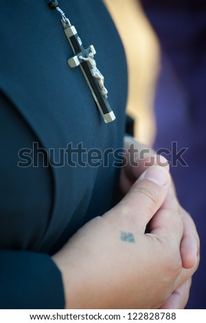 A Catholic nun wears a crucifix necklace and a tattoo of a cross on her hands, which are folded in prayer. - stock photo
