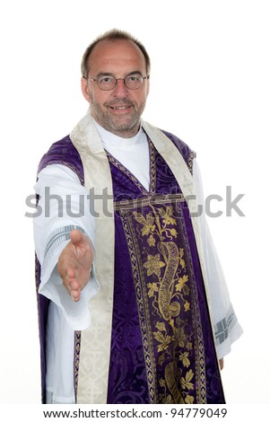 a catholic priest extends his hand in greeting.