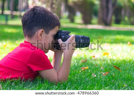 A caucasian boy is interested in the art of photography. A boy in a red t-shirt lies on grass outdoors holding a digital camera, trying to focus on a distant object. Sunny September morning in a park.