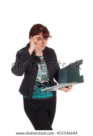 A Caucasian business woman standing with her clipboard in her hand and