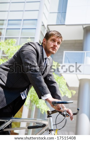 A caucasian businessman riding a bike to work, can be used for green or gas savings concept - stock photo