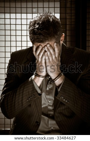 A caucasian businessman sitting in jail handcuffed - stock photo