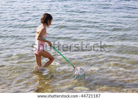 a caucasian child catching jellyfish with a net - stock photo