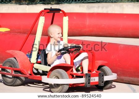 a caucasian child undergoing cancer teatment having fun on a go cart at a fun fair - stock photo