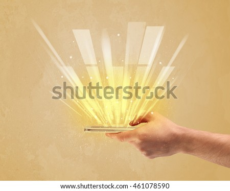 A caucasian hand holding a tablet phone with light beams and information escaping the device illustration concept