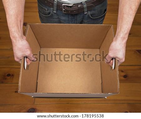 A caucasian male holding an empty cardboard box. - stock photo