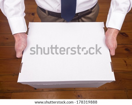 A caucasian male holding an office box. - stock photo