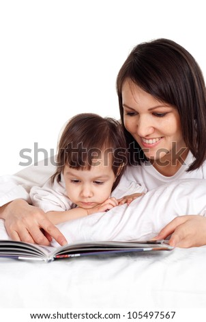 A Caucasian mama with her daughter lying on the bed with a book