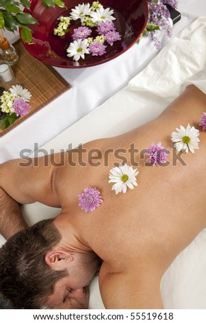 A Caucasian man lies on a massage table with flowers down his back.