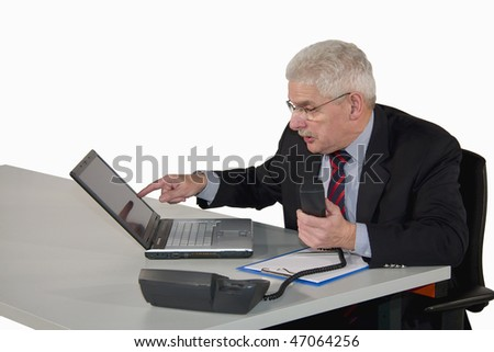 a caucasian senior manager being busy phoning and pointing at his laptop, isolated on white background