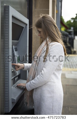 A caucasian Woman withdrawing money from ATM machine.