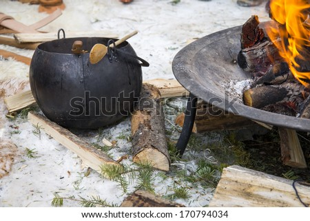 A cauldron resting on the ground next to a fire - stock photo