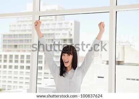 A celebrating business woman with her arms raised up in the air - stock photo