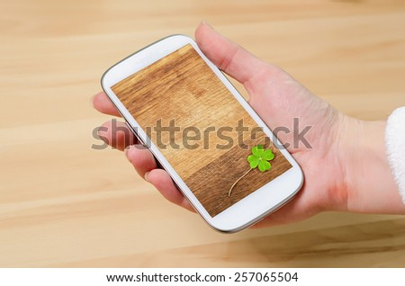 a cellphone with clover on display, st.patricks day - stock photo