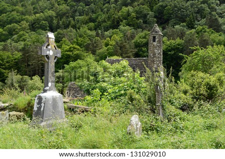 A celtic cross on the overgrown graveyard next to the medieval church of St. Kevin at the monastic heritage site Glendalough, south of Dublin in Ireland. - stock photo
