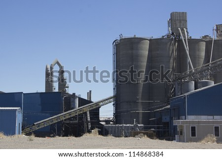 A cement plant with silos and blue skies.