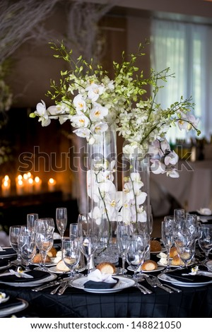A centerpiece floral arrangement of white orchids highlights the table setting at a wedding reception. - stock photo