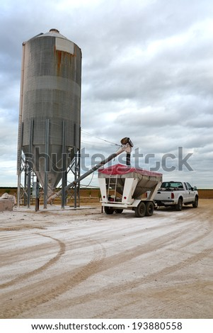 A Central California farm trailer is loaded with gypsum from a silo in order to protect and enrich soil. - stock photo