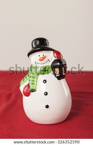 A ceramic art piece shaped snow man for christmas(x-mas) on the red fabric at the studio. - stock photo