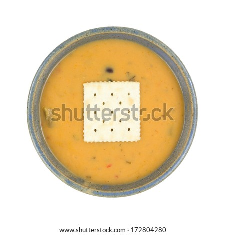 A ceramic bowl of tomato soup with a  smooth blend of cheese and seasonings and cracker on top.. - stock photo
