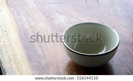 A ceramic bowl on a wood table.