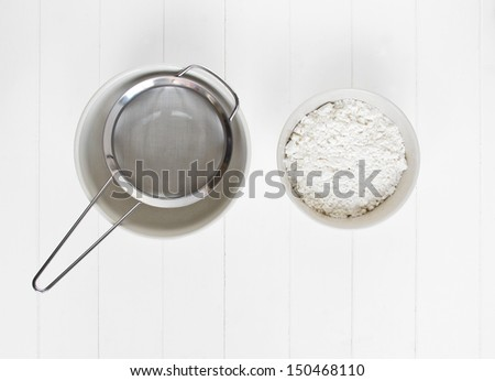 A ceramic bowl with white flour sits ready to be sifted (sieved) though a metal sieve, on white wood.