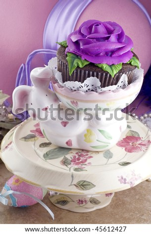 A ceramic Easter bunny holding a beautifully decorated cupcake with a purple rose, on a pretty spring cake stand, vertical with copy space