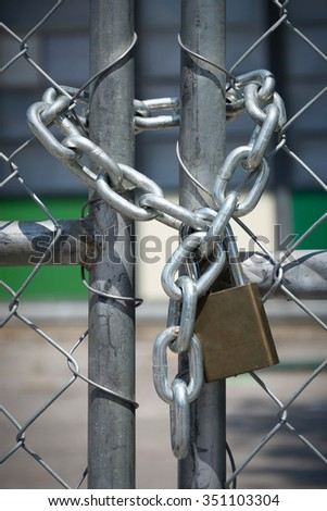 A chain and pad locks secures an entry way fence. - stock photo