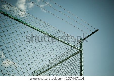 A chain link fence, topped by razor wire. Horizontal shot - stock photo