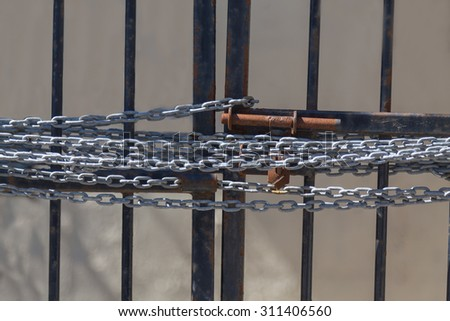 A chain on a gate preventing access to the inside