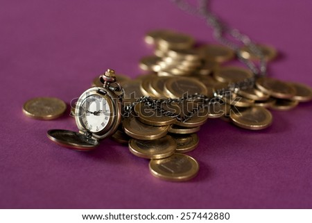 A chain watch and euros on a blurred purple background - stock photo
