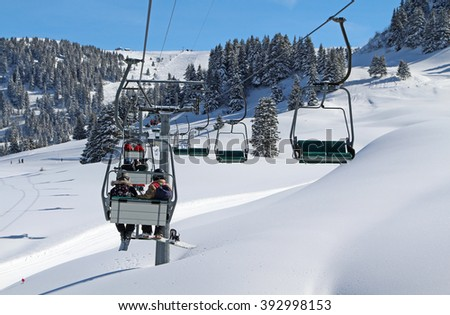 A chair lift transports skiers and snowboarders up a slope in a ski resort at Villars in the Swiss Alps.