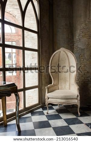 A chair near window on checker floor - stock photo