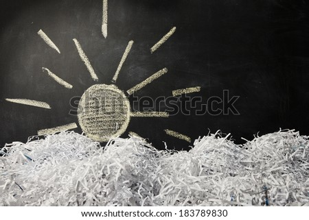 A chalk drawing of a sun behind a landscape made of shredded paper. - stock photo