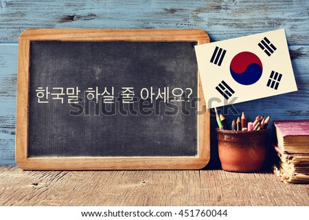 a chalkboard with the question do you speak Korean? written in Korean, a pot with pencils, some books and the flag of South Korea, on a wooden desk - stock photo